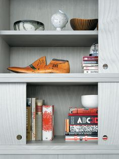The cabinet doors of the living room wall unit, in birch veneer painted a calming gray, slide with silken ease but never fully close, leaving strategic gaps…