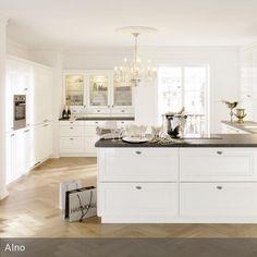 Der Arbeitsbereich der offenen Küche in Weiß dient zugleich als Abgrenzung zum Flur. Das Möbelstück ist so tief, dass sowohl auf der Küchen- als auch auf…