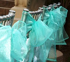 I love the silver chairs with the sparkly ribbon bows :)
