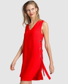 Vestido corto, en color rojo, sin mangas y escote de pico. Con cierre de cremallera en la espalda y crucetas con arandelas en los costados.