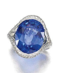 SAPPHIRE AND DIAMOND RING.  Set to the centre with an oval mixed-cut sapphire within an elliptical frame decorated with brilliant-cut diamonds, size L, French assay and maker's marks, two small diamonds deficient.