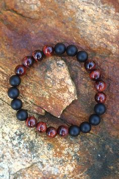 Let your inner fire burn with intensity. Be strong and remain focused on your goals. This bracelet contains the gemstones Onyx and Red Tigereye. Stones are 8mm each. Strong elastic (.8mm). Need help to find your size? Click here to read the MalaRae bracelet sizing guide.
