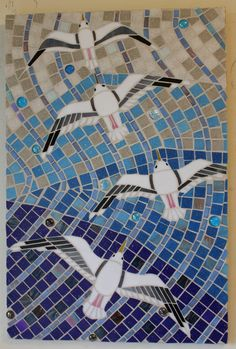 This unique glass mosaic features four seagulls gliding overhead and is titled Gliding Gulls. You can almost smell the ocean with this beautiful piece!  The background for this piece was made with vitreous glass tiles which are darker blue in the front, fading to a beige in the distance. The gulls were created using stained glass.  This beachy mosaic was created using medium density fiberboard (MDF) as the base, its dimensions are 16 by 24, it is finished and signed on the back by me, and…