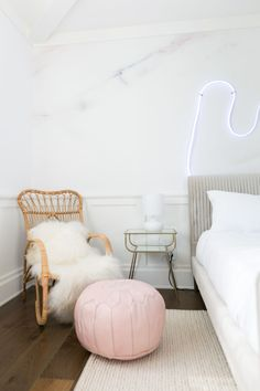A rattan chair with sheepskin pillows and a pink ottoman bring bohemian flair to a seating area.