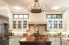 The bright kitchen is equipped with a Sub-Zero refrigerator, a Wolf range, and a classic farmhouse sink. Diy Kitchen Decor, Kitchen Furniture, Kitchen Design, Home Decor, Farmhouse Furniture, Kitchen Layout, Wolf Range, Above Kitchen Cabinets, Kitchen Countertops