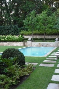 brick retaining wall, grass around jacuzzi with pavers. I also like the terraced landscaping above the wall