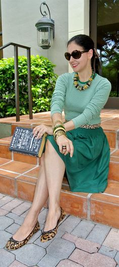 Susana Fernandez | A Key to the Armoire - An interesting outfit. There are some things I'm not so keen about (the book clutch, the animal print), but I love the green skirt with the striped top and the bling