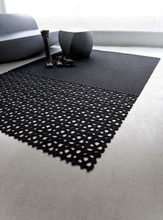 *product design, modern interiors, carpets* - RIVER ROCK CARPET BY BEV HISEY.  The River Rock carpet is a die cut wool felt rug that reveals the flooring beneath the perforations. The smooth end of the carpet really highlights the river rocks on the other side.: