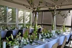 Fresh and beautiful centerpieces of white and green blooms with asparagus, green and deep red grapes, green apples, crab apples and fig branches.