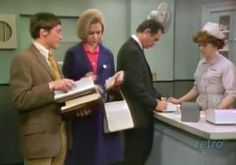 Maggie rifles through her mail while Matt signs in at the desk.