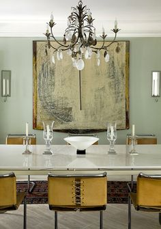the contrast between the art, the chairs and the sleek table makes the room so interesting