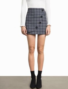 """Grey Plaid Mini Skirt with Curved Button Detailing. Made by us65% polyester, 35% rayon with liningLength 15.5""""Fit is high waistModel is wearing a size small an"""