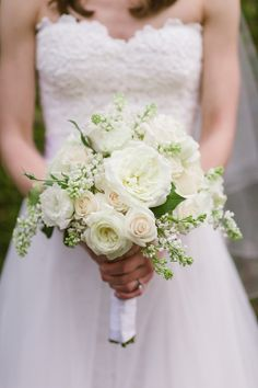 The bride will carry a textured clutch bouquet of white hydrangea, white lilac, ivory garden roses, white freesia, white lisianthus, queen anne's lace, white ranunculus, and variegated pittosporum wrapped in ivory ribbon and lace with the stems showing