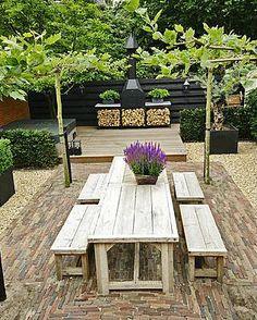 kleine leeftuin met grote tafel en tuinhaard en houtopslag achterin