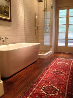 Modern tub, glass enclosed shower, tribal runner, painting over tub