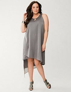 Angled layers of pebbled satin and sheer chiffon define this Lane Collection high-low dress with elegant edge. Confidence is in every inch of this dramatic silhouette, featuring keyhole detailing at the neckline and a buttoned keyhole back. Sleeveless. lanebryant.com