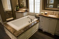 Dark marble countertops over white wood cabinetry match the twin vanities with…