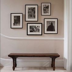 The start of a gallery of black and white photographs traditional hall bench and a warm wall colour make this space by @rlaxterinteriors.