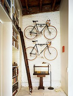 super tall bookshelf with a sliding ladder? hanging bike racks for displaying your cool vintage road bike? whitewashed brick wall? love,love,love