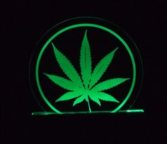 "$42 - Green, Marijuana Leaf Edge lit acrylic art: Be the chronic envy of your buds with this unique piece of art! A mellow green glow will envelop your space, giving you great mood lighting.     Frosted Acrylic has been laser frosted and lit from below with long lasting green LED lights.     This piece throws off enough light to move around the room by, providing enough light to find your stash box, or lighter!    Wooden base, Dimensions are 6"" wide by 8"" tall."