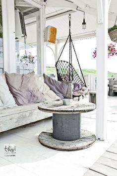 stolik na balkon ze starej szpuli po kablach,meble z recyklingu na taras,drewniane siedziska z poduchami z odzysku,wiszący ażurowy fotel kokon,stare taborety i stołki z patyną,rustykalne meble vintage na tarasie,jak urządzić taras z pomalowanymi na biało stołami, stołkami z patyna,meble i dekoacje z patyną w stylu vintage,tarasowe meble i dekoracje w białej patynie vintage,styl vintage w dekoracji tarasu,biały taras,białe aranzacje tarasowe i balkonowe