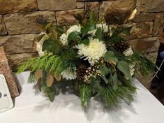 With gold and seasonal greenery accents, white flowers and pinecones.