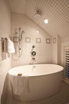 A gorgeous and huge freestanding tub becomes an excellent shower as well with the addition of shower heads, both waterfall and handheld. White tile covers the walls, ceiling and floors in a 360-degree backsplash.