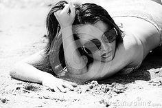 Hispanic girl in swimsuit lying on the sand