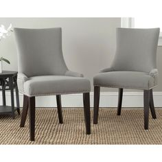 These gorgeous Lester dining chairs by Safavieh feature beautiful nailhead detailing and elegant, gentle sloped arms with a slight hourglass shape. Upholstered in a modern granite gray linen, these chic chairs will lend posh style to your dining room.
