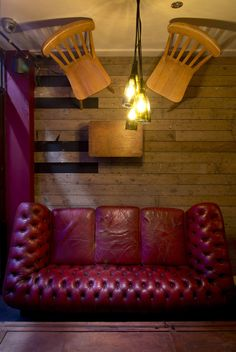 Wine bar Cellar Magneval in Fleet, Hampshire, UK. Featuring off the wall furniture including red leather sofa and reclaimed wooden furniture