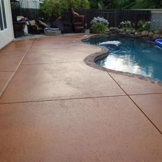How to apply multi-color concrete stain. Love the rocks against the back of pool with greenery.