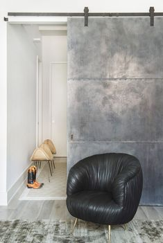 A stylish corner with a sliding metal door and a leather armchair