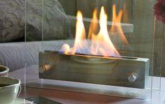 Etna Table Fireplace. Etna Table Fireplace è un piccolo camino da tavolo che, grazie all'etanolo, crea della fiamme all'interno di due piastre di vetro senza creare fumi e odori. Ideale per sorprendere e accogliere gli ospiti del vostro salotto.