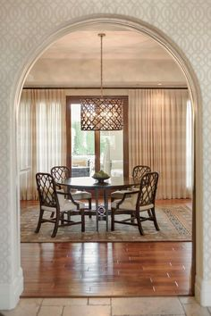 A graceful archway invites diners to relax in the casual dining area under the intricate penn shell chandelier. Curtains covering a wall of windows and doors can be opened to allow natural lighting in or drawn to create a more intimate dining setting.