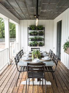 """""""Black iron planters, a black iron light fixture and a custom metal sign personalized the outdoor patio and made it a perfect space for family dinners together,"""" says designer Joanna Gaines."""
