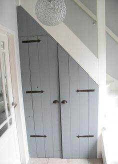 Stoere grijze inbouwkast onder de trap
