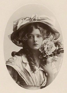 Idyllic antique photo of a young girl with large hat and flowers near her face, fabulous.