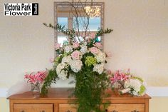 Arrangement designed with White Hydrangea, Stock, Pink Roses, and Curly Willow and Various Greens centered by Stargazer Lilies featuring our lovely Bridal Bouquet arranged with Blush Peonies and White and Green Hydrangea