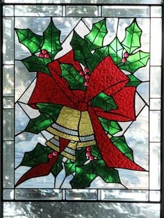 """Three Bells, Holly, and Bow"" is a 20 ½"" x 25 ¼"" original stained glass art piece designed and created by Lynne Provance. This piece uses rough rolled, wispy, English muffle, ½"" nuggets, and bevels. This piece brings a festive winter holiday flair as it hangs in the window. A ¼"" grinder bit was used for detailing."