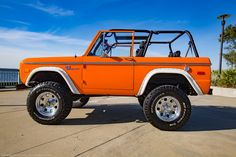 Orange Classic Ford Bronco with Coyote V8 engine and many other upgrades recently restored by Velocity Restorations in Pensacola, FL.
