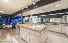 Elegant: An enviable open-plan kitchen area has a hob and sink on a centre island and pale...