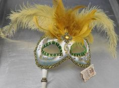 A beautiful original Venetian Mask with - -hand printed musical notes -gold glitter swirl motifs -edged in gold embroidery ribbon -green around the eyes and cheek bones -rhinestone in the center forehead -beautiful airy feathers flower above the mask -12 long wooden handle for right hand to hold  The original tag is still attached and reads-  La Maschera del Galeone  A real Venice hand made product. Artists have realized and decorated it in full respect of artisan traditions and original…