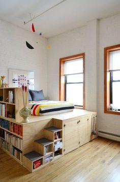 Кровать-подиум который включает в себя и систему хранения под кроватью и книжные полки отгораживающие спальное место от остальной части комнаты. .
