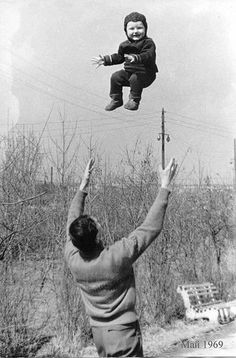 vintage dad throwing son baby high into air
