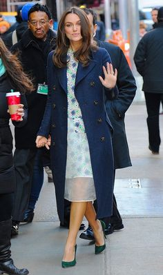 Keira Knightly wears a structured floral dress, fitted navy blue coat and suede green heels.