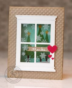 Grand Madison Window by Poppy Stamps. Stamp snowflakes with StazOn ink onto acetate rectangle. Let dry. Glue acetate behind window. Cut rectangle in card front with rotary paper cutter. Shade window a bit with Copic. Create scene inside card so that it shows through window. Add snow hill at bottom of scene so that you have room to write a message. Outside sentiment is embossed in white and anchored with a heart.  By Jennifer McGuire
