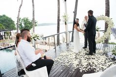 White gazebo wedding with flowers in heart shape and ocean as backdrop.