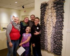 """John Skare, Bricelyn, Minnesota, in the exhibition. Handwoven rya wall hanging, 1987. """"Mona took this photo of the kids and me by my rya weaving that the Vesterheim purchased in 1987. I remember Marion Nelson relating this piece to the ryas that were placed in the bottom of the long boats. Perhaps my heritage was creeping into my artworks without my knowledge. I hadn't seen this piece since 1987. A reunion for me with one of my creations. A bit emotional. I like this piece. It was…"""