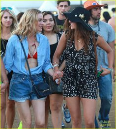 Nina Dobrev holds hands with her pal Diane Kruger as they walk around during the second weekend of the 2015 Coachella Music Festival