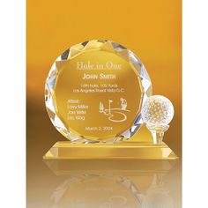 """A clear, round, decorative edged, glass plaque on a flat base with a teed clear, glass golf ball. Great for golf outings and tournaments. 8"""" W x 7 1/2"""" H x 3/4"""" D."""
